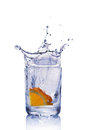 Splash in glass of blue water with orange slice Royalty Free Stock Photo