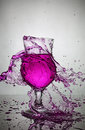Splash in glass of purple alcoholic cocktail drink Royalty Free Stock Photo