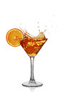 Splash in glass of transparent alcoholic cocktail drink with slice orange and ice Royalty Free Stock Photo