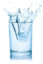 Splash from ice cube in a glass of water. Royalty Free Stock Photo