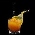 Splash splashing out of a glass with juice on a black background Royalty Free Stock Photography