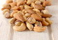 Splashed nuts mix on the wooden table selective focus on the front Royalty Free Stock Photos