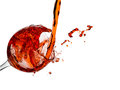Splashes red wine splashing while pouring into a glass Stock Photos