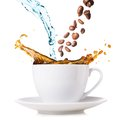 Splashing coffee hot is in cup water and beans are blending Royalty Free Stock Photography