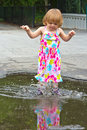Splashing girl puddle jumper two year old in a colorful summer dress jumping and in a at a park type of area Stock Photography