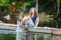 Splashing in a lake teenage girl sitting on dock water Royalty Free Stock Image