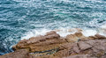 Splashing ocean waves crashing against bare rocks Royalty Free Stock Photo