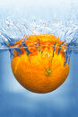 Splashing orange into a water Stock Photos