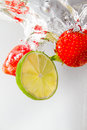 Splashing strawberry and lime fresh slice into water Stock Photo