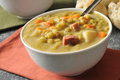 Split pea soup with chunks of ham and a dinner roll Royalty Free Stock Photos