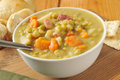 Split pea soup with ham carrots and potatoes on a rustic wooden counter Stock Photography