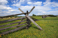 Split rail fence under blue sky a in a meadow of green grass and yellow buttercup flowers a with white clouds in virginia Stock Photo