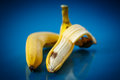 Spoiled banana peeled on a blue background Royalty Free Stock Photo