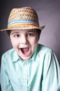 Spoiled child close up studio portrait of a shouting boy in hat concept of Royalty Free Stock Photos