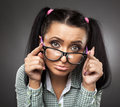 Spoiled nerd brat sulky girl with glasses and pigtails posing as a on gray background Royalty Free Stock Image