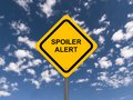 Spoiler alert written in black on yellow road sign against blue sky and clouds Royalty Free Stock Photography