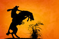 Spooked stallion silhouette of cowboy reigning bucking bronco by something in the nearby sagebrush sunset orange yellow textured Stock Photo