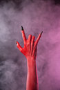 Spooky devil hand showing heavy metal gesture studio shot on smoky background Royalty Free Stock Photos