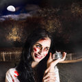 Spooky girl with silver service bell in graveyard creepy deceased zombie woman holding a location a depiction of death services Stock Photos
