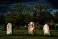 Spooky old graves weathered headstones in a rural nineteenth century cemetery glow eerily under a darkening sky wiht a grainy Royalty Free Stock Image