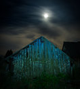 A spooky old wooden barn at night illuminated with full moon
