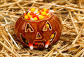 Spooky pumpkin filled with candy corn on straw Royalty Free Stock Photo
