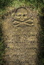 Spooky tombstone an old ancient grave stone with skull and crossbones Royalty Free Stock Photo