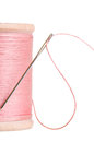 Spool of pink sewing thread with needle Stock Photo