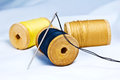 Spool of thread and needle on fabric Royalty Free Stock Photo