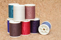 Spools of thread multicolored on cork board Stock Photos