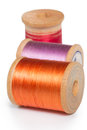 Spools of thread three colorful orange purple and red nylon on white background Stock Photography