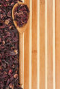 Spoon with dried hibiscus on a bamboo mat space for text for menu Royalty Free Stock Photography