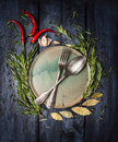 Spoon and fork on plate with herbs and spices frame on dark blue wooden table top view Royalty Free Stock Images