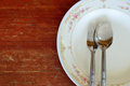 Spoon and fork with white plate on wood table Stock Photos