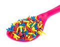 Spoon full of colorful candy sprinkles a pink filled with on a white background Royalty Free Stock Images