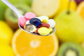 Spoon full of colorful pills Royalty Free Stock Photo