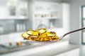 Spoon full of fish oil capsules on kitchen background Royalty Free Stock Photos