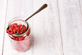 A spoon an full jar of superfood goji berries on white wood table Royalty Free Stock Photo