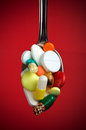 Spoon full of various pills Stock Photo