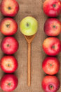 Spoon with green apple lying on the sackcloth among red apples as background Stock Images