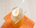 Spoon with honey above glass jar on orange napkin Royalty Free Stock Photos