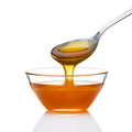 Spoon of honey on the white Royalty Free Stock Photos