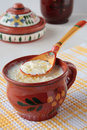Spoon of milk soup with noodles and cup butter in a ceramic bowl Stock Image