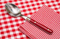 Spoon and napkin with red and white checks on a table cloth Stock Image