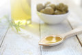 Spoon with olive oil next to an oilcan and some natural green olives. Royalty Free Stock Photo