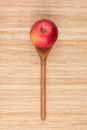 Spoon with red apple lying on the bamboo mat as background Royalty Free Stock Photos