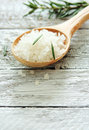 Spoon of sea salt closeup over wood background Stock Images