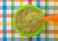 Spoonful of baby food above bowl Royalty Free Stock Photo