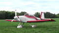 Sport airplane isolated small red and white on a grassy field on white Stock Images