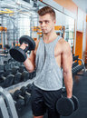 Sport bodybuilding training and people concept young man with dumbbell flexing muscles men working with dumbbells his body at gym Royalty Free Stock Images